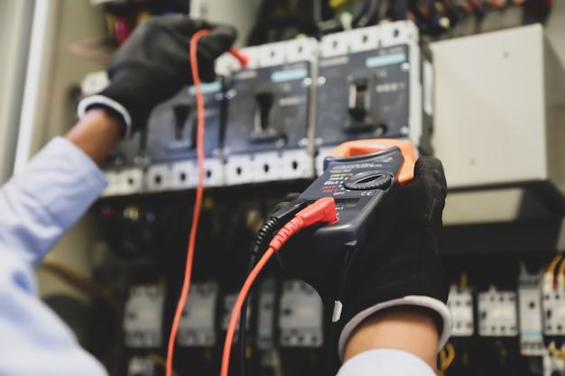Elektrotechniker mit digitalem multimeter zur überprüfung der stromspannung am leistungsschalter