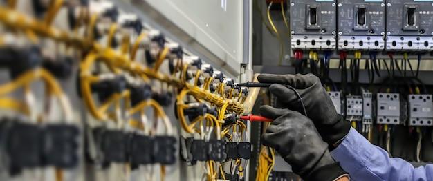 Elektrotechniker mit messgeräten zur überprüfung der elektrischen stromspannung am leistungsschalter