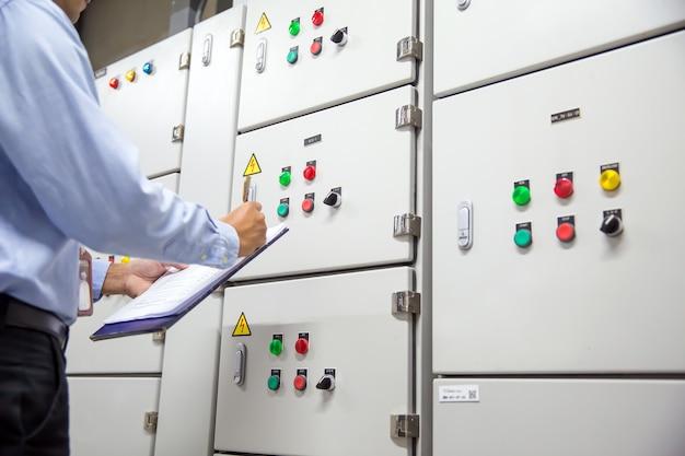 Elektrotechniker prüft den anlasser-schaltschrank des lüftungsgeräts.