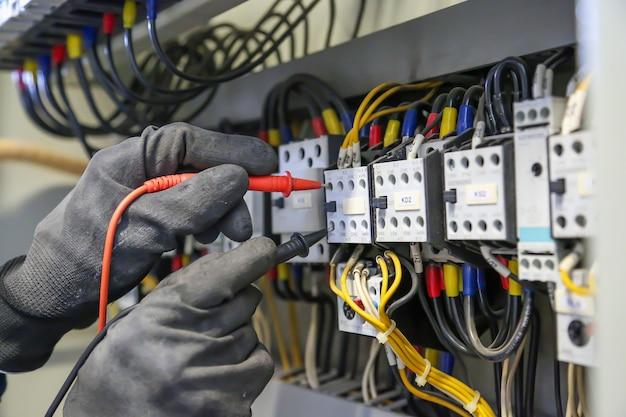 Elektrotechniker verwendet digitales messgerät zur überprüfung der elektrischen stromspannung am leistungsschalter.