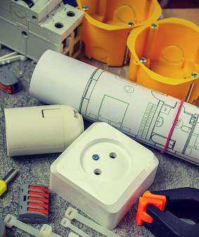 Elektrowerkzeuge und eine reihe von komponenten für die verwendung in elektroinstallationen auf einer grauen oberfläche mit einem platz für text