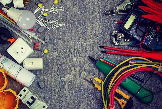 Elektrowerkzeuge und eine reihe von komponenten zur verwendung in elektroinstallationen auf grauem hintergrund mit einem platz für text