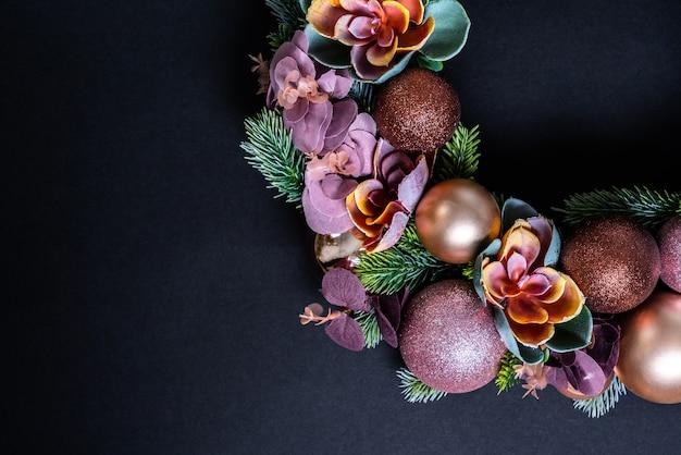 Elemente der weihnachtskranzdekoration auf schwarzem. flach liegen