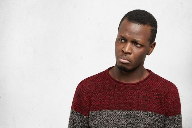 Elender erbärmlicher junger afrikanischer mann, der kurz davor steht zu weinen, sich unglücklich und verärgert fühlt