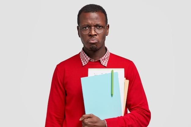 Elender, missfallener, beleidigter schwarzer männlicher student, will vor negativen emotionen weinen, trägt ein lehrbuch mit einem stift und hat es satt, zu studieren