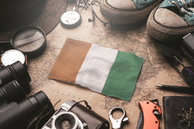 Elfenbeinküste-flagge zwischen dem zubehör des reisenden auf alter weinlese-karte. touristisches bestimmungsort-konzept.