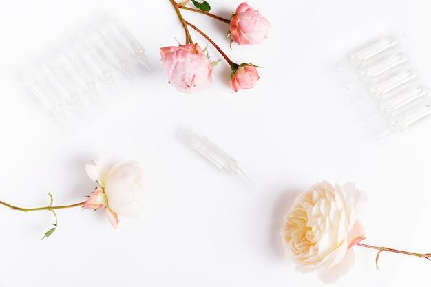 Elite-gesichtspflegeprodukt in ampulle und rosen auf weißem hintergrund. ampulle für kosmetik
