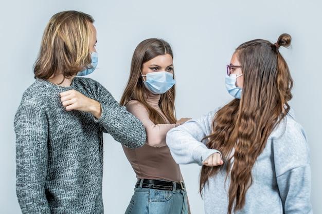 Ellbogen stoßen. freunde, die eine schützende gesichtsmaske tragen und sich gegenseitig mit dem ellbogen begrüßen. menschen freunde stoßen ihre ellbogen, coronavirus, soziale distanz und freundschaftskonzept.
