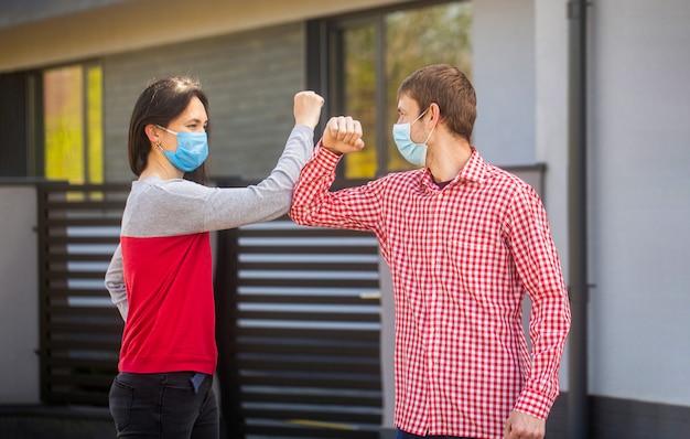 Ellbogen stoßen. freunde in schützender medizinischer maske auf seinem gesicht begrüßen ihre ellbogen in quarantäne.