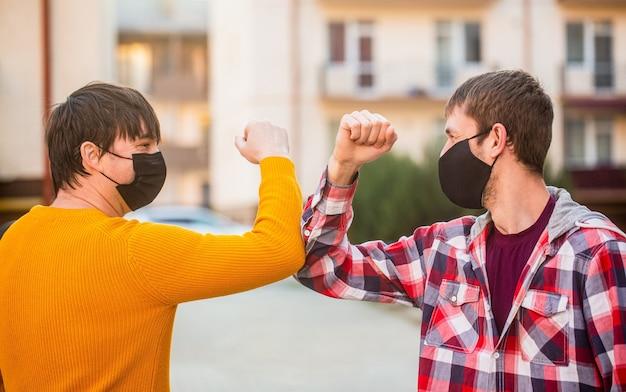 Ellbogenstoß bekämpfen sie die ellbogen des coronavirus im freien