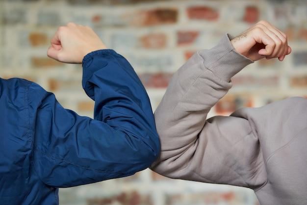 Ellenbogen stoßen. ein junge und ein mädchen stoßen an die ellbogen, anstatt mit einer umarmung oder einem händedruck zu grüßen