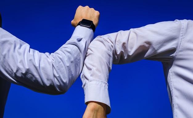 Ellenbogen stoßen. eine neue art der begrüßung, um die ausbreitung des coronavirus covid-19 zu vermeiden. zwei personen, ein mann und eine frau, stoßen an die ellbogen, anstatt sich zu umarmen oder sich die hand zu geben