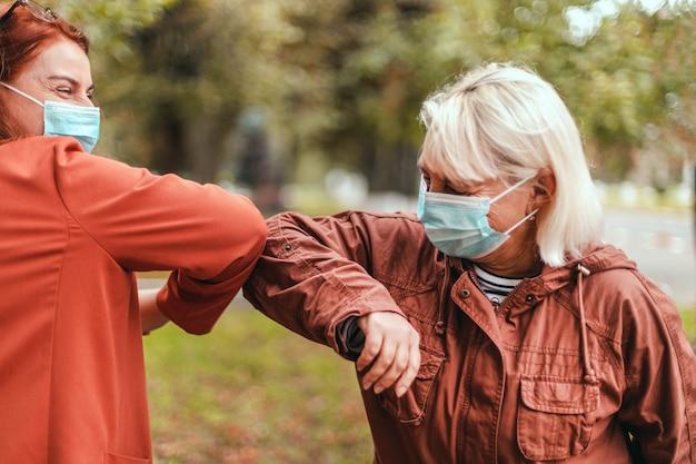 Ellenbogenstoß zwei personen stoßen an den ellbogen, um coronaviren im freien zu vermeiden.