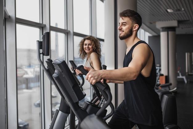 Elliptical walker trainer mann und frau im fitnessstudio, übung?