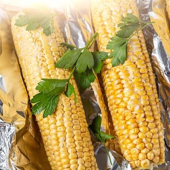Elote mais bestreut mit käse oder parmesan, koriander, gewürzen und chili auf backblech