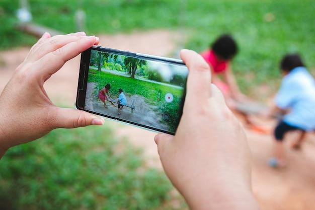 Eltern benutzen telefone, um ihre kinder beim schaukeln zu fotografieren.