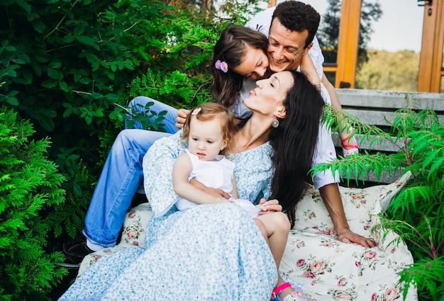 Eltern bewundern ihre kleinen kinder, die mit ihnen auf schritten draußen sitzen