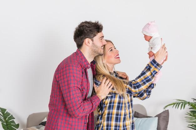 Eltern, die baby in den händen betrachten