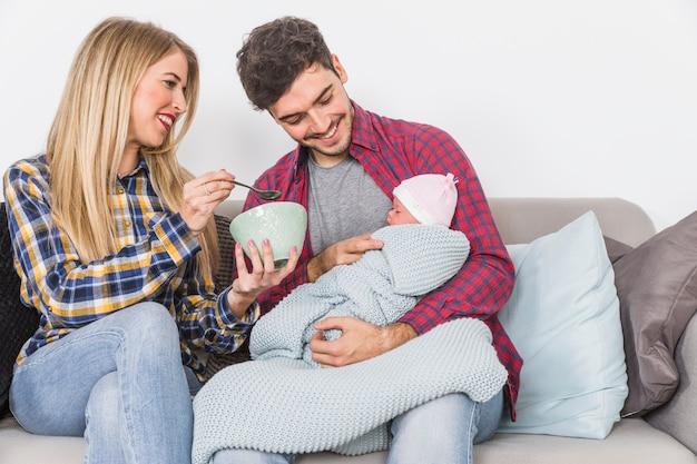 Eltern, die baby mit löffel füttern