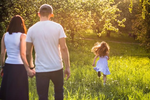 Eltern, die ihr mädchenkind laufen in park betrachten