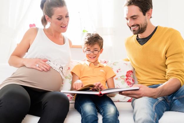 Eltern, die ihre erstgeborenen sohnbilder im familienalbum zeigen