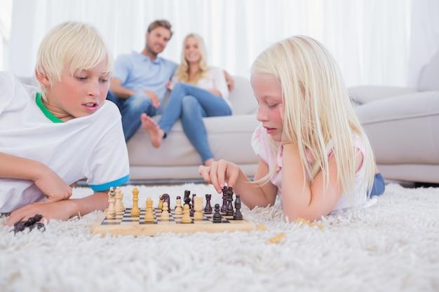 Eltern, die ihre kinder betrachten schach betrachten