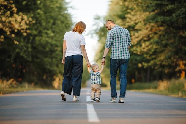 Eltern, die ihren kleinen sohn halten, gehen eine straße entlang