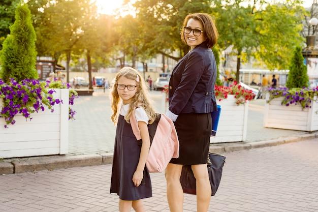 Eltern, die kind an der hand halten, gehen zur schule