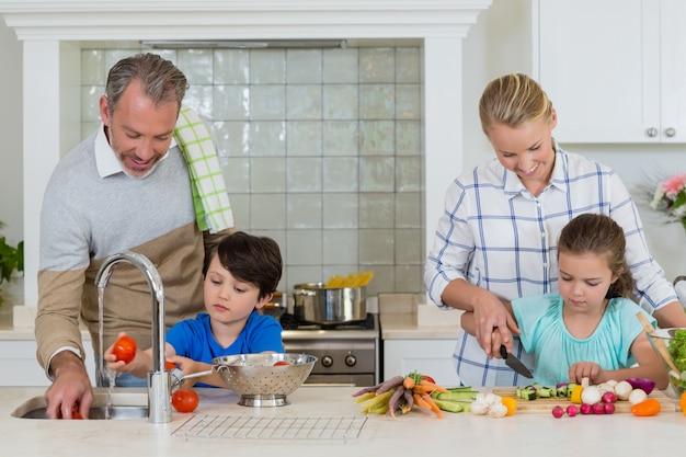 Eltern, die kindern helfen, das gemüse in der küche zu hacken und zu reinigen