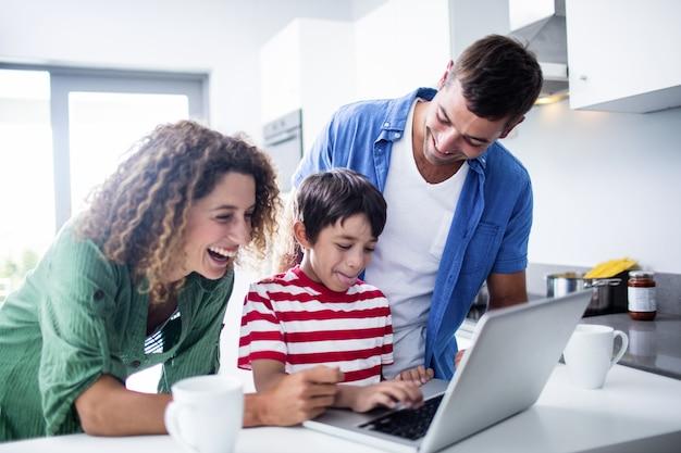 Eltern, die laptop mit sohn in der küche verwenden