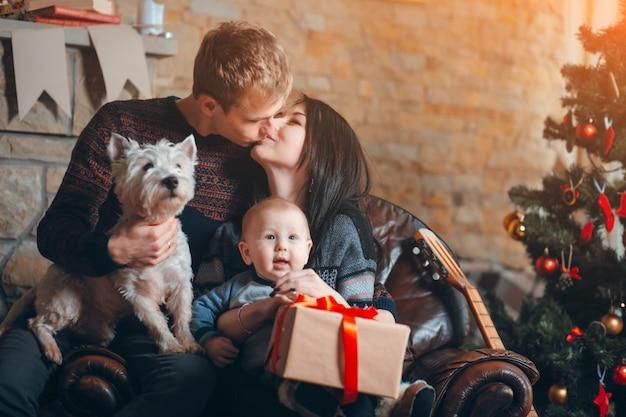 Eltern, die mit einem hund und einem baby mit einem hintergrund weihnachtsbaum
