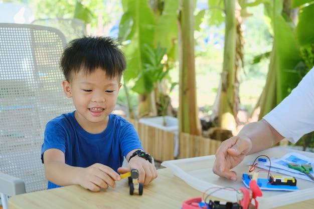 Eltern, die mit kleinem kind zu hause sitzen, asiatischer vater und sohn, die spaß haben, machen spielzeugauto mit recycelten materialien zu hause im hinterhofgarten auf natur, stammbildung, lernen zu hause, spaßige heimschule