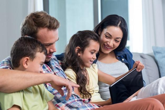 Eltern, die mit sohn und tochter sitzen und digitale tablette betrachten