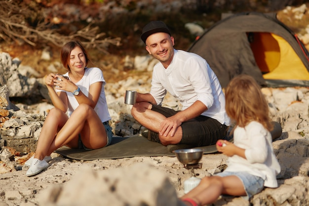 Eltern, die nahe zelt sitzen, tee trinken und kleine tochter betrachten.