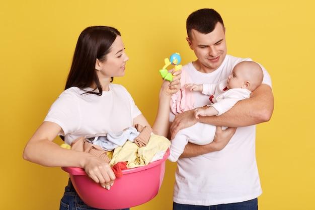 Eltern, die sich um das neugeborene kind kümmern, während sie hausarbeiten und wäsche erledigen, mutter mit dunklem haar, das ihrem kleinen kind sitzsack zeigt, fetter hält baby in händen, lokalisiert über gelbem hintergrund.