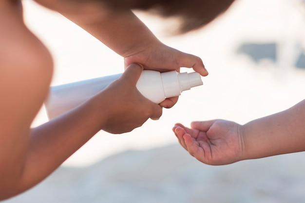 Eltern, die sonnencreme in der hand des kindes anwenden