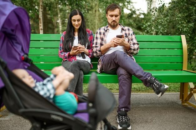 Eltern, die telefone benutzen, während sie mit kleinem baby im sommerpark spazieren gehen