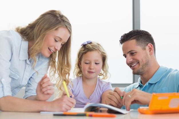 Eltern, die tochter bei der zeichnung bei tisch unterstützen