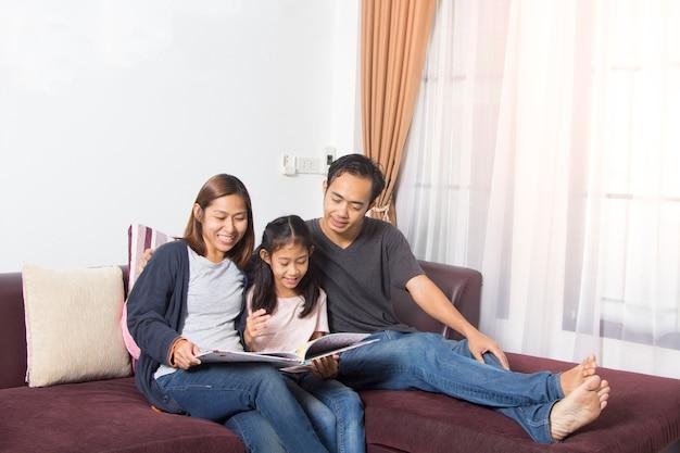 Eltern, die zuhause mit tochterlesegeschichte sitzen