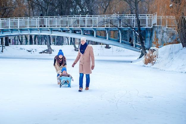 Eltern fahren ihre tochter auf einem schlitten und haben spaß, gefrorenen see vor dem hintergrund der brücke
