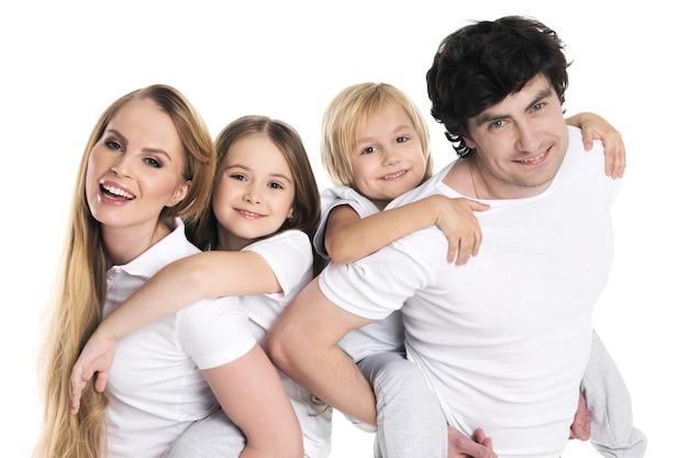 Eltern geben zwei kinder huckepackfahrten lächelnd isoliert auf weißer wand