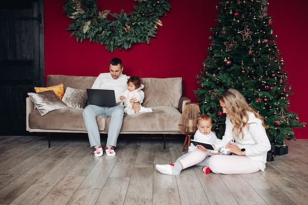 Eltern halten ihre kinder und betrachten bildschirme ihrer elektrischen geräte in der nähe von weihnachtsbaum