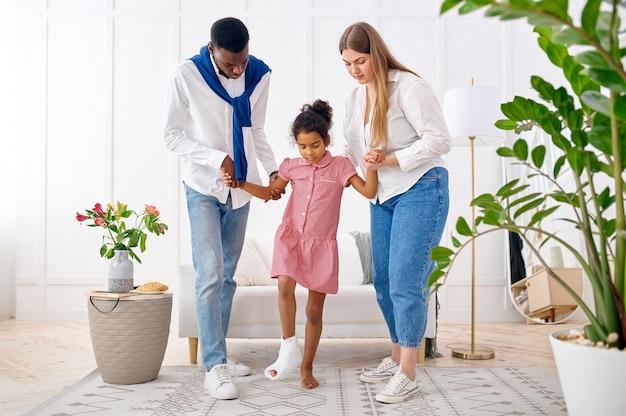 Eltern helfen einem kleinen mädchen mit einem gebrochenen bein im wohnzimmer. mutter, vater und ihre kleine tochter bewältigen den ärger gemeinsam, elterliche fürsorge