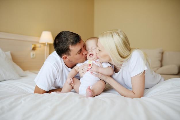 Eltern küssen das baby im bett