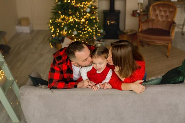 Eltern küssen ihre tochter an silvester vor dem hintergrund eines weihnachtsbaumes
