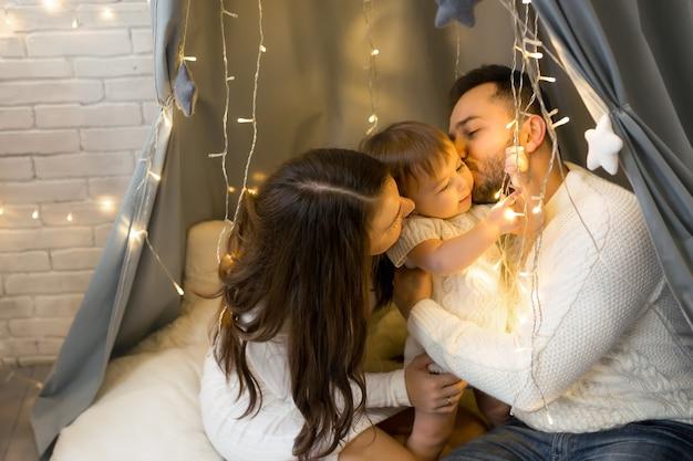 Eltern küssen ihre tochter, während sie unter einer weihnachtsgirlande aus lichtern sitzen
