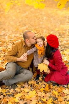 Eltern küssen ihre zweijährige tochter auf die wange, die auf den trockenen gelben blättern sitzt