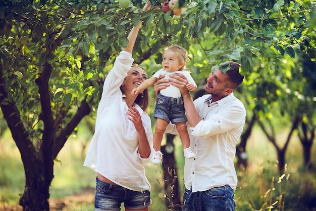 Eltern mit baby genießen picknick auf einem bauernhof mit apfel- und kirschbäumen.