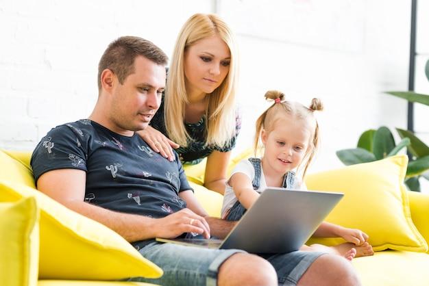 Eltern mit der kleinen tochter, die zu hause laptop im wohnzimmer verwendet