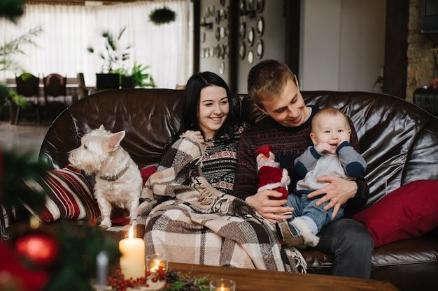 Eltern mit einem baby zu weihnachten und ein hund sitzt auf der couch